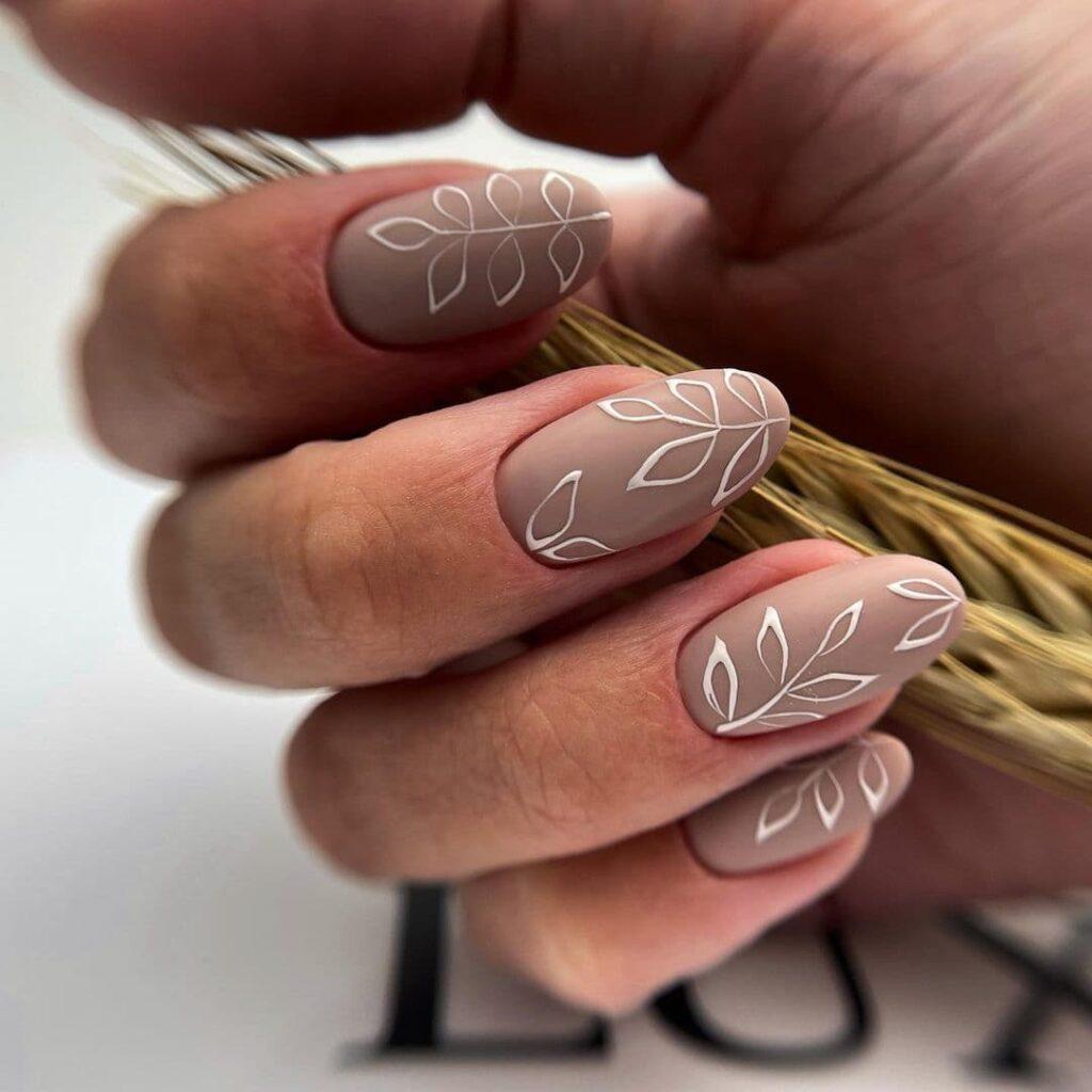 Матовый бежевый осенний маникюр с листьями