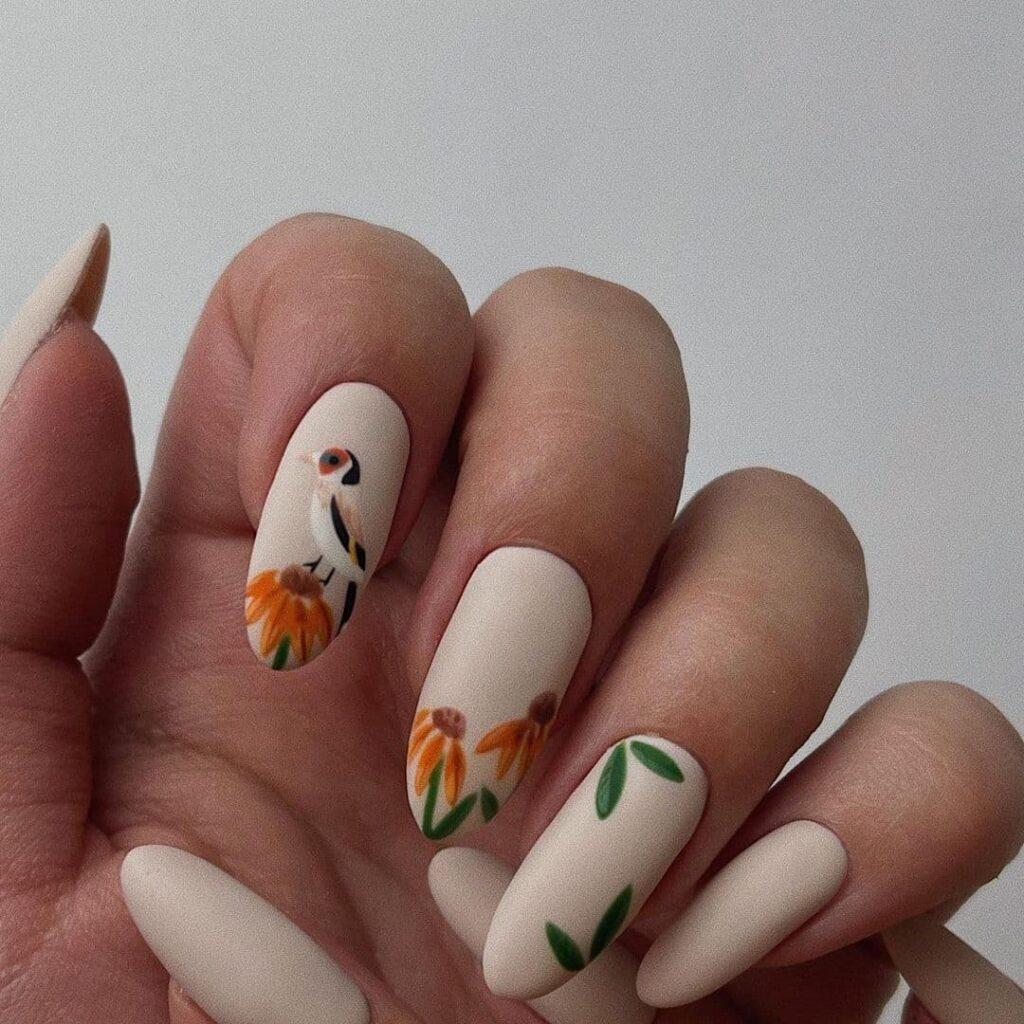 Бежевый матовый маникюр с ромашками и птицей